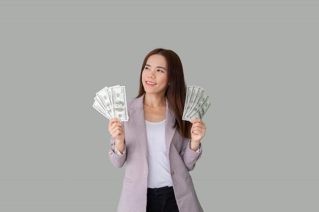 Портрет улыбающегося красивая азиатская женщина, держащая много денег банкноты