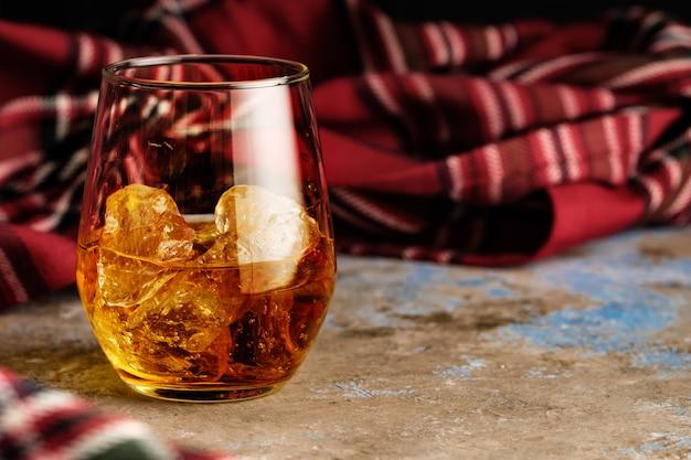 バーボンのグラスのある静物。氷とウイスキーのグラス。秋の脾臓の概念