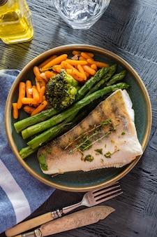 Филе судака со спаржей, брокколи и морковью. жареная рыба с тушеной зеленью