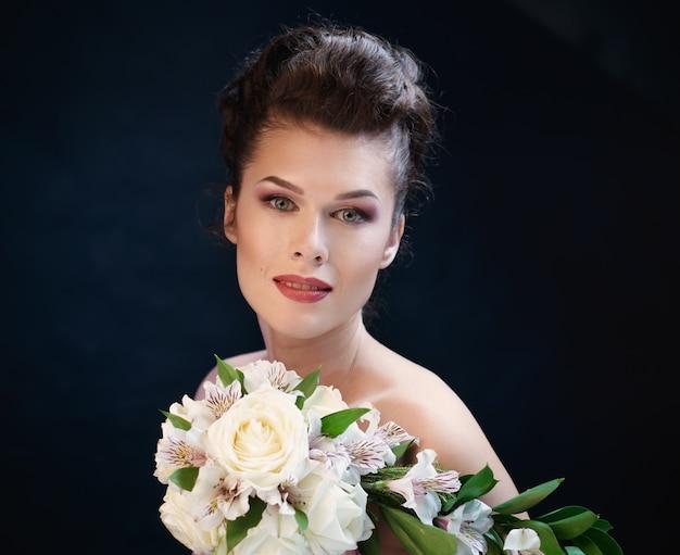 バラと蘭の花束を持つ若いかわいい笑顔の女性。