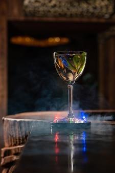 Прозрачный алкогольный коктейль с мятой на барной стойке