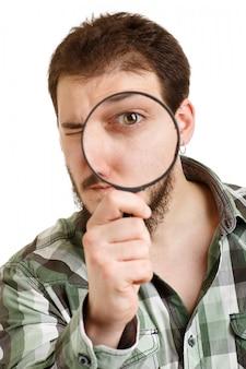 虫眼鏡を通して見る緑のシャツの男。