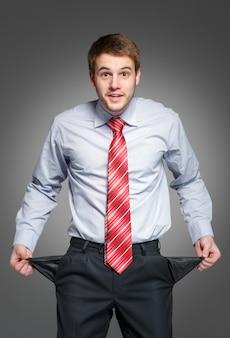 彼のポケットを裏返しにして、彼の空のポケットを示す実業家