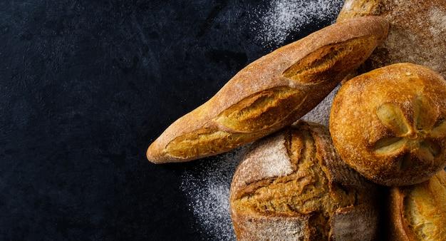 暗いテーブルの上の焼きたての自家製パンと組成の平面図。