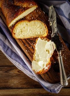 スライスしたハラとバターは、伝統的なユダヤ人の甘い新鮮な安息日パンです。