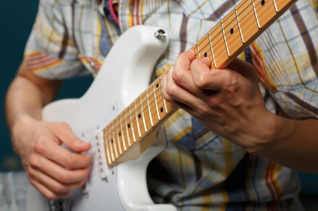 ギターを弾き、弦の一部にセレクティブフォーカス