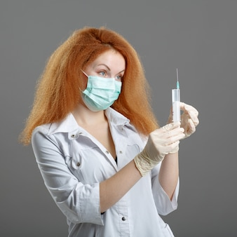 ヘルスケアと医療のコンセプト-女性医師または看護師医療マスク持株シリンジ注射器