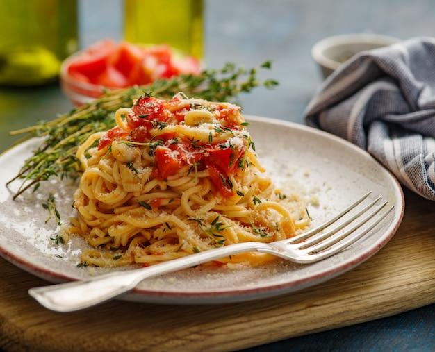 青いテーブルの上の皿にタイムとトマトのスパゲッティ