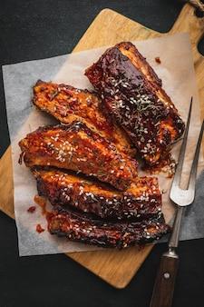 Очень вкусные зажаренные нервюры барбекю на разделочной доске, взгляд сверху. традиционные американские свиные ребрышки копченые