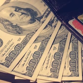 木製の上のクレジットカードとドル紙幣と茶色の財布。