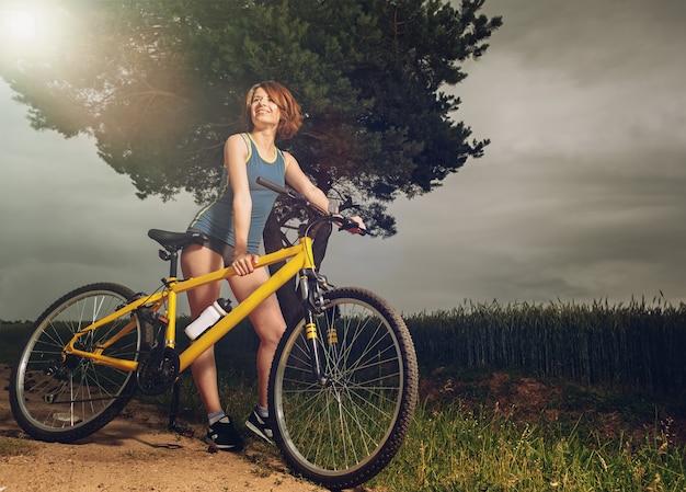 Красивая спортивная девушка, стоя с велосипедом за городом.