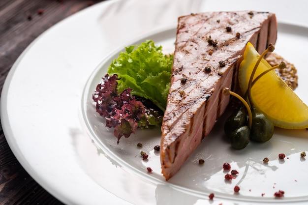 木製テーブルの上のレモンとケッパーの調味料と新鮮なグリーンサラダと丸い白いプレートに揚げマグロステーキ