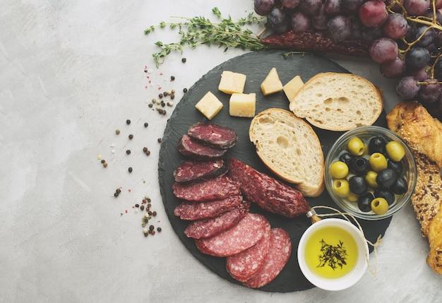 素朴なスタイルでスライスしたサラミ。サラミソーセージ。チーズ、ブドウ、オリーブの異なるソーセージ。トーン、トップビュー
