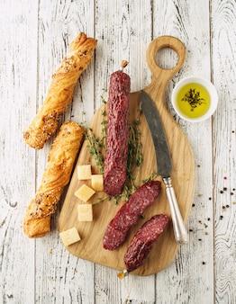 素朴なスタイルでスライスしたサラミ。サラミソーセージ。チーズとオリーブの異なるソーセージ。上面図。
