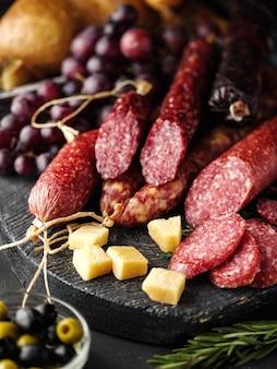 素朴なスタイルでスライスしたサラミ。サラミソーセージ。チーズ、ブドウ、オリーブの異なるソーセージ