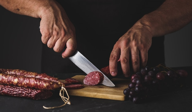 Мужские руки режут колбасу салями на разделочную доску.