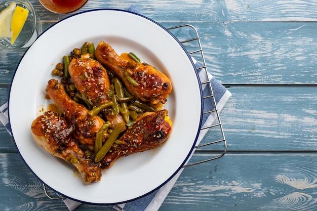 エンドウ豆、豆、新鮮なハーブと焼き鶏の脚。おいしいソースと野菜のチキンドラムスティック