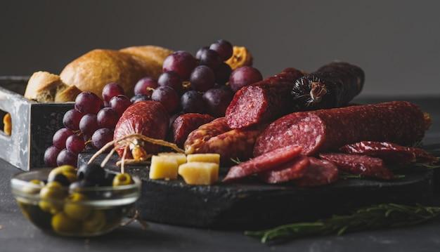 チーズ、ブドウ、オリーブの異なるソーセージ。素朴なスタイルでサラミをスライス