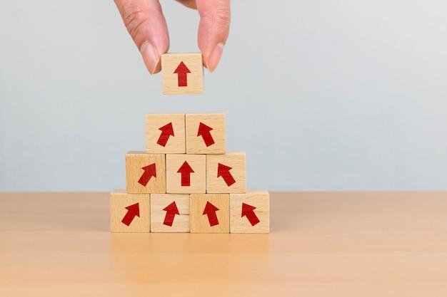 Лестница карьеры для концепции роста успеха бизнеса. рука, укладка деревянных блоков, как шаг лестницы со стрелкой вверх
