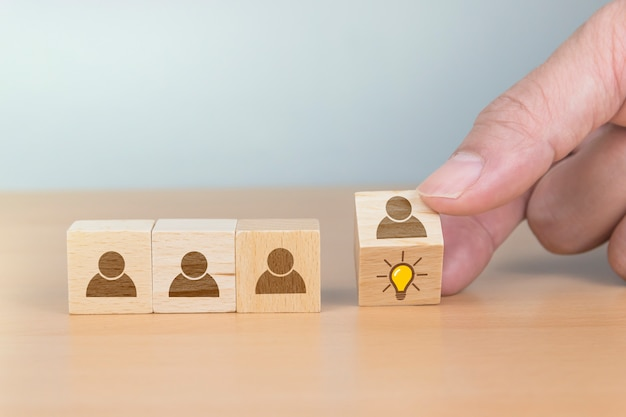 Концепция творческой идеи и инноваций. рука перевернуть деревянный куб с головой человека символ и значок лампочки