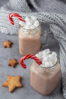 Две кружки с горячим шоколадом и зефир с имбирным печеньем на сером фоне