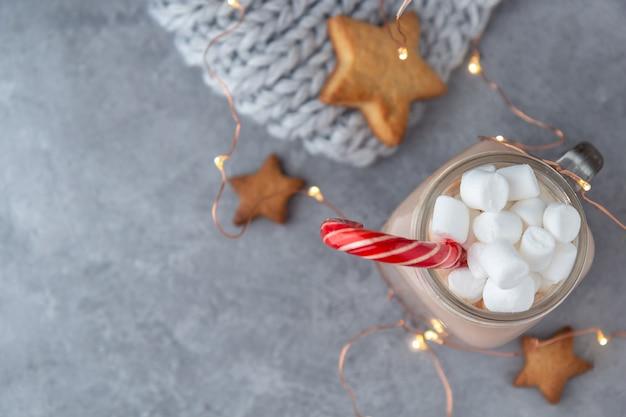 Какао с маршмеллоу и сахарный тростник на сером фоне с печеньем и вязаный шарф с гирляндами.