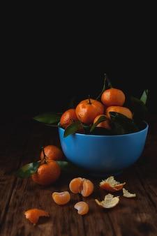 Мандарины вишни в миску на деревянном столе.