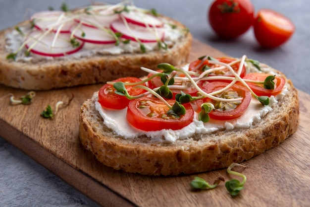 灰色の表面に野菜、マイクログリーン、穀物パンのサンドイッチのクローズアップ