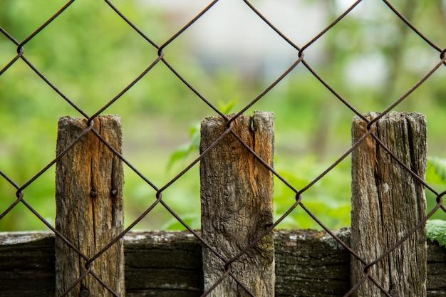庭と金属メッシュの古い木製のフェンス