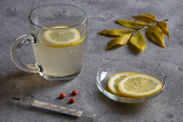 Имбирный чай с лимоном, лимоном и листьями на сером