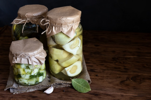Консервы овощные в баночках на деревянном столе