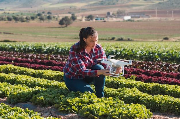 ドローンとレタスの分野で働く若い技術的な女性
