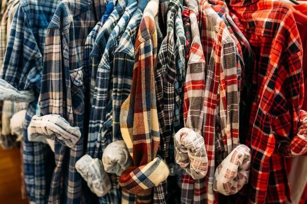 ハンガーに掛かっているレトロなカラフルな格子縞のシャツの列が付いている棚。