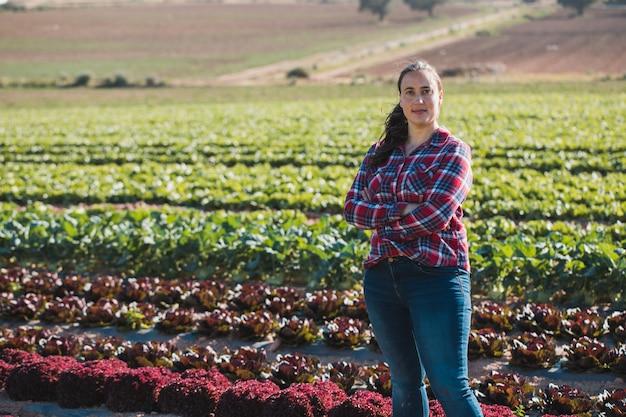 レタスの分野でカメラを探している若い技術的な女性
