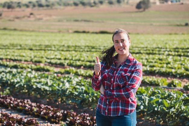 笑顔とレタスの分野で親指でカメラを探している若い技術的な女性