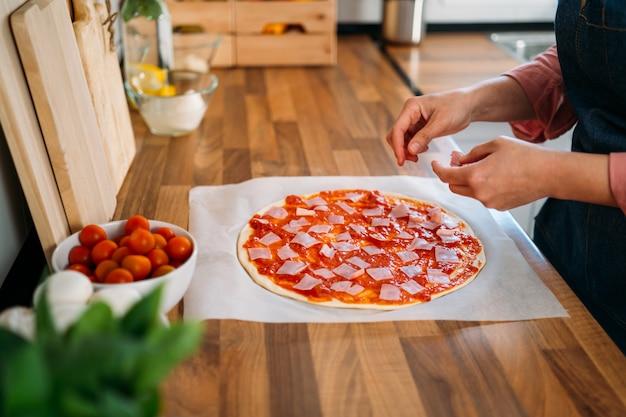 Женщина готовит традиционную итальянскую пиццу