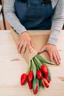 Флорист делает букет из красных тюльпанов и упаковывает их в пачку бумаги на деревянный стол
