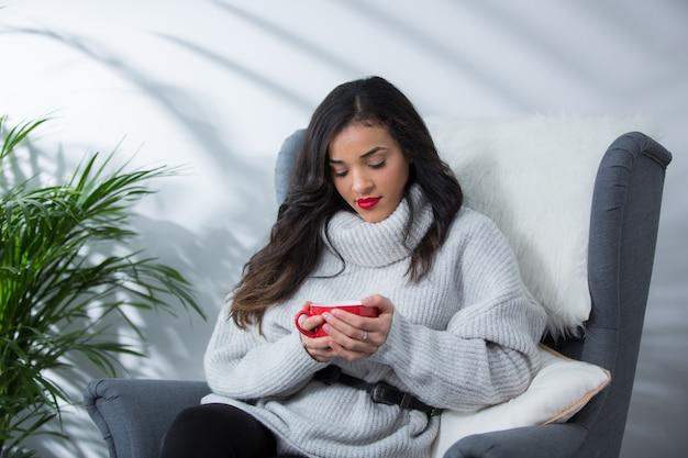 暖かいダイニングルームで彼女のソファーに座っていた赤カップでホットコーヒーを飲んで幸せな女