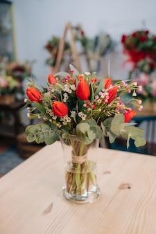 木製のテーブルに素敵な赤とオレンジのチューリップの花束