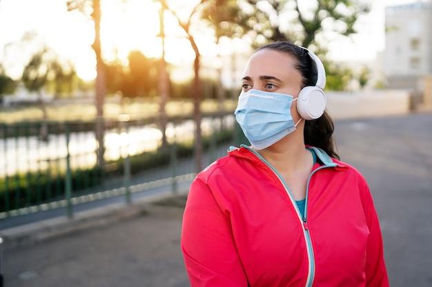 日没時に医療用マスクとヘッドフォンを身に着けている若い女性ランナー