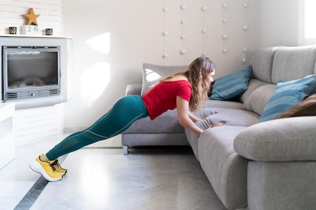 Женщина занимается спортом, делая отжимания на диване у себя дома