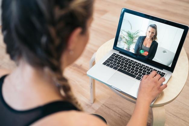 女性従業員の背面図、オンラインブリーフィングで同僚とビデオ通話で話す、女性労働者が自宅のラップトップで仲間とオンライン会議をする