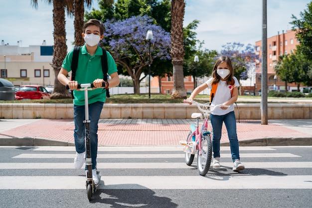 男の子と女の子のマスクを着用し、スクーターや自転車に乗って通り
