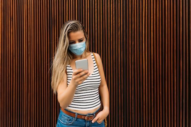 コロナウイルスのパンデミック時に携帯電話を使用して街のマスクをした女性
