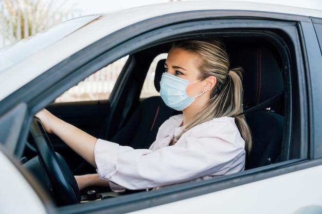 Женщина с маской за рулем автомобиля во время пандемии коронавируса