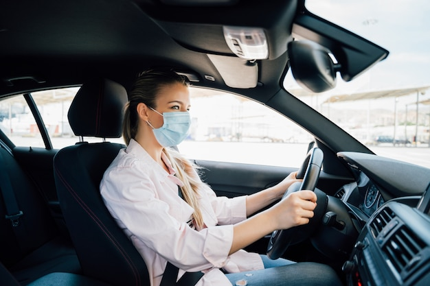 コロナウイルスのパンデミック中に彼女の車を運転してフェイスマスクを持つ女性