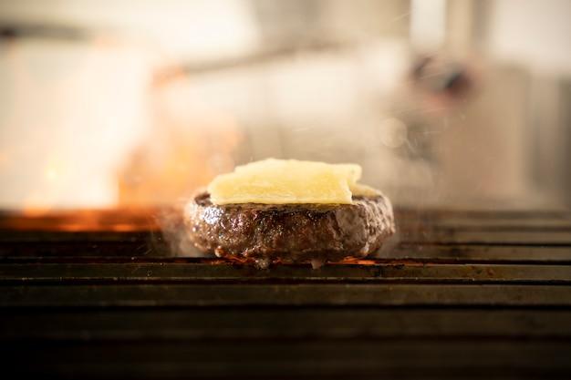 グリルでおいしいチーズハンバーガーのクローズアップ。
