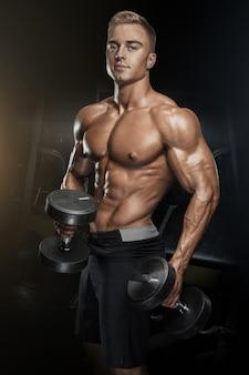 Красивый спортивный парень тренировки с гантелями