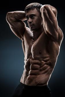 黒の背景にポーズをとってハンサムな筋肉ボディービルダー