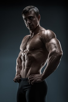 筋肉とフィットの若いボディービルダーフィットネス男性モデルのポーズ。